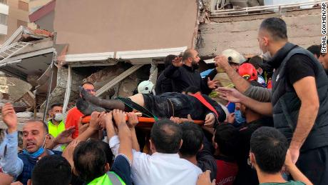 Rescue workers and locals carry a wounded man found in the rubble of a collapsed building in Izmir, Friday.