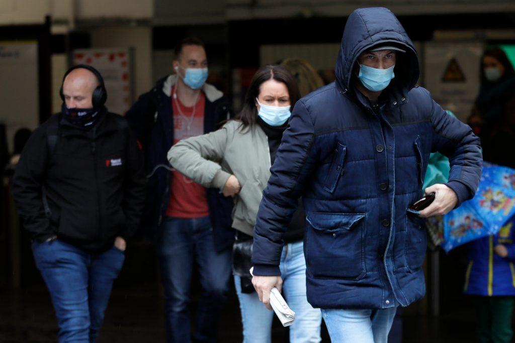 Commuters wear masks as they leave a tube station in London