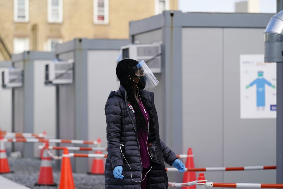 A worker wearing a face shield walks between portable units intended for registration and testing at the New York City COVID-19 Test Site for Hospitals + Health in the Brooklyn area of New York, Thursday, November 19, 2020. (AP Photo / Cathy Wellins)
