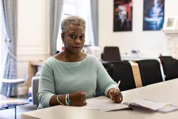 Mrs. Donna Kinnear, CEO and Secretary General of the Royal College of Nursing, sits at a table, writes on a piece of paper and looks at the camera.
