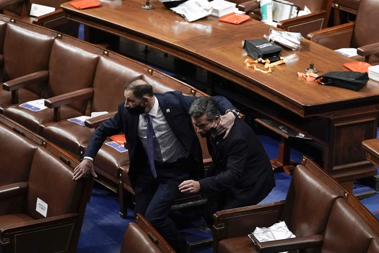 Parliamentarians in House conference rooms bow their heads to search for hiding places as Trump supporters flood Parliament.  Photo: AP.