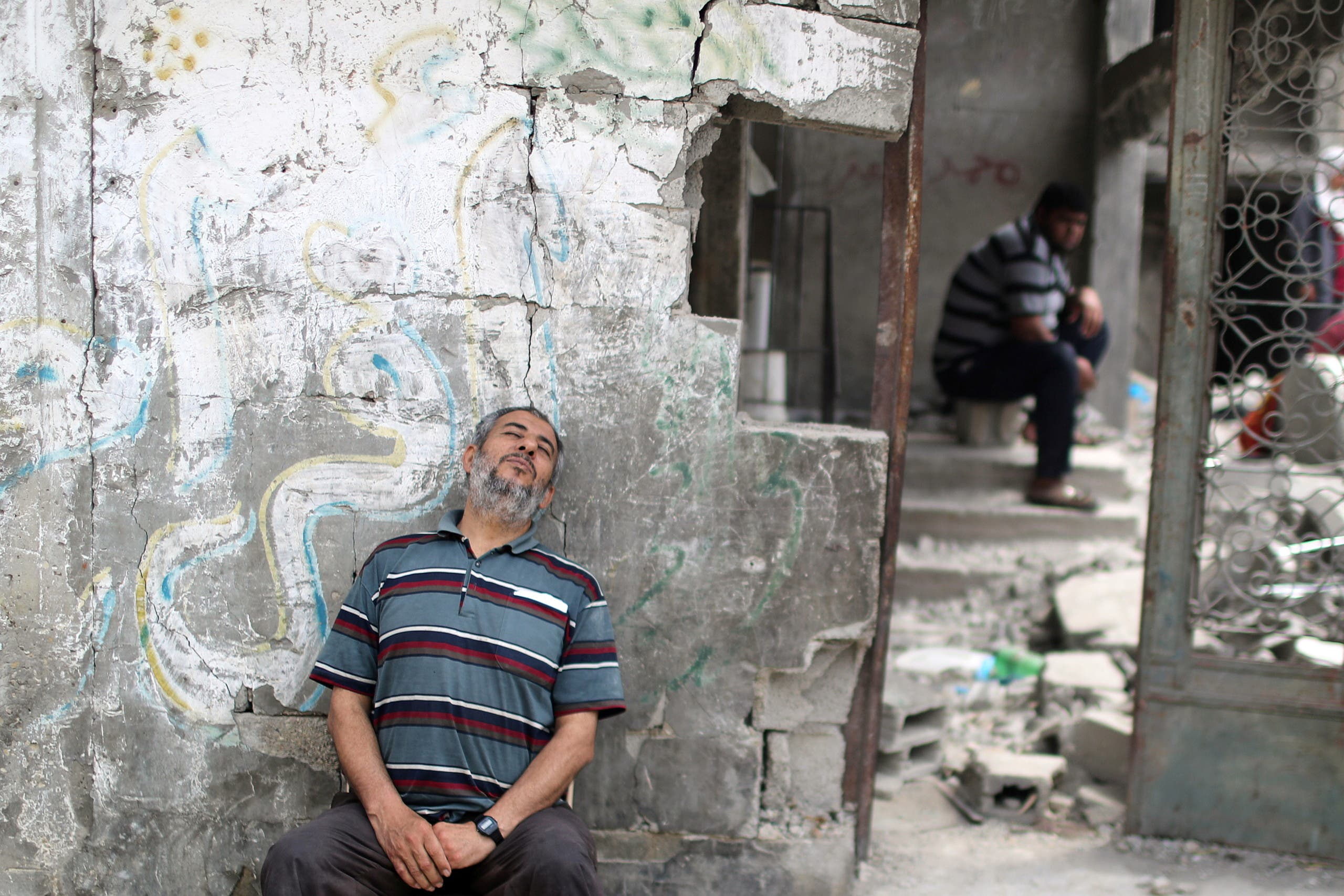 A Palestinian sits beside the rubble of his house in Gaza