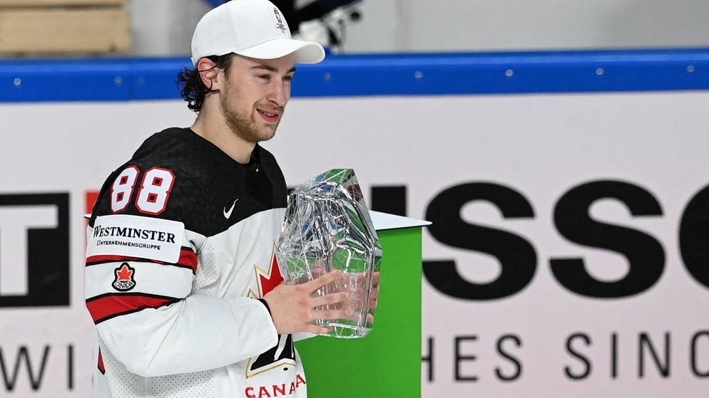 Canadian striker Andrew Manjiabani poses with the trophy for best player during the ceremony after the IIHF Men's World Ice Hockey Championship final match between Finland and Canada at Arena Riga in Riga, Latvia, on June 5, 2021. - 3-2 win over Finland Canada crowned the 2021 Ice Hockey World Champions (Photo by Gints IVUSKANS / AFP) (Photo by GINTS IVUSKANS / AFP via Getty Images)