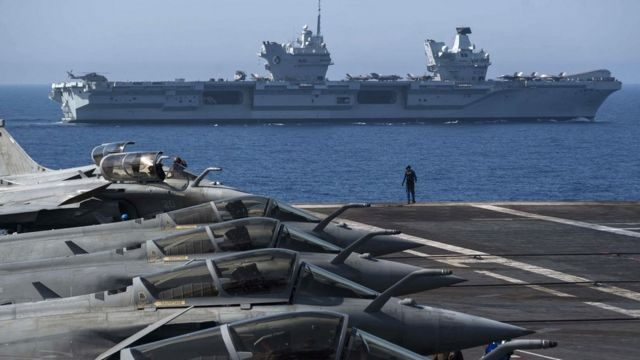 """French Navy Rafale fighters sit on the bridge of the French aircraft carrier Charles de Gaulle with the British Royal Navy aircraft carrier HMS Queen Elizabeth in the background during naval exercises """"heavy blow"""" Off the coast of Toulon, southeast France on June 3, 2021."""