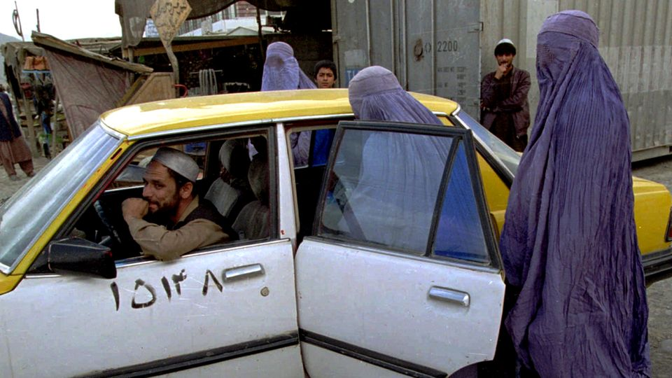 Afghanistan: Two women in light blue burqas climb into the back of a white and yellow taxi on a street in Kabul