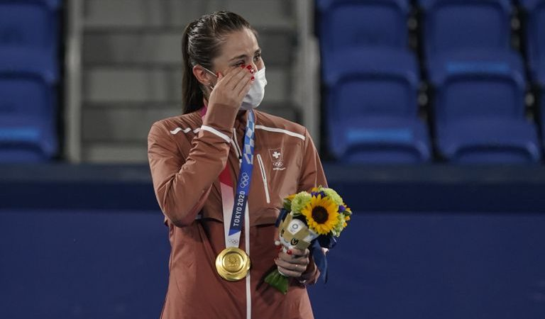 La suiza Belinda Bencic llora en el podio tras recibir la medalla de oro en el tenis individual de los Juegos Olímpicos, el domingo 1 de agosto de 2021, en Tokio (AP Foto/Seth Wenig)