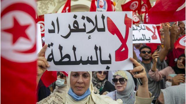 Demonstrators raise the phrase