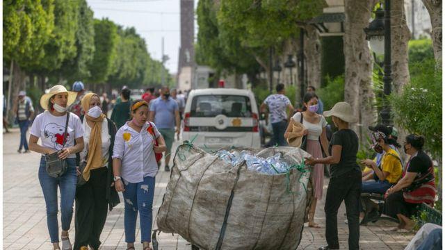 Tunisians walk on Habib Bourguiba Avenue in the center of the Tunisian capital