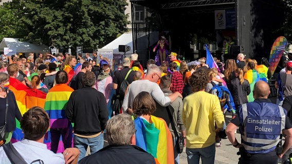 People dressed in colorful clothes are standing in front of the stage.  © NDR Photo: Jutta Przygoda